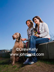 Couple sits in the park with their two dogs, a Chihuahua and a Weimaraner,